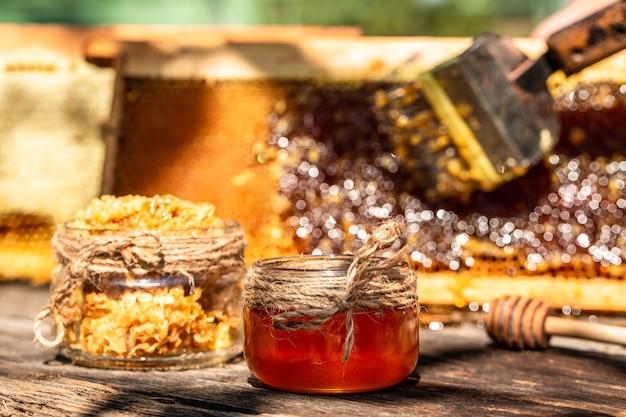 Натуральный мед в сотах и стеклянная банка на деревянном столе