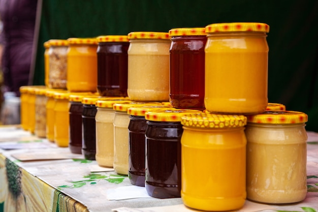 Natural honey in glass jars on the market. jars with various kinds of pure, raw, fresh honey.