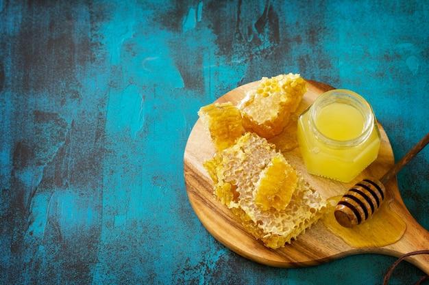 ガラスの瓶とひしゃくの天然蜂蜜蜂蜜青い石のテーブルの甘いハニカムコピースペース