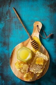 ガラスの瓶とひしゃくの甘いハニカムの天然蜂蜜蜂蜜