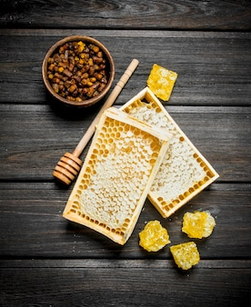 木製のテーブルの上のハニカムの天然蜂蜜。