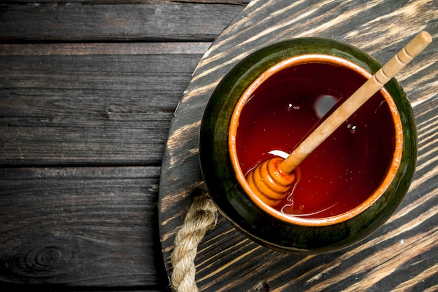 Натуральный мед в горшочке на деревянном столе.