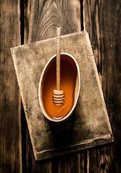 Натуральный мед в деревянной бочке с ложкой. на деревянном фоне.