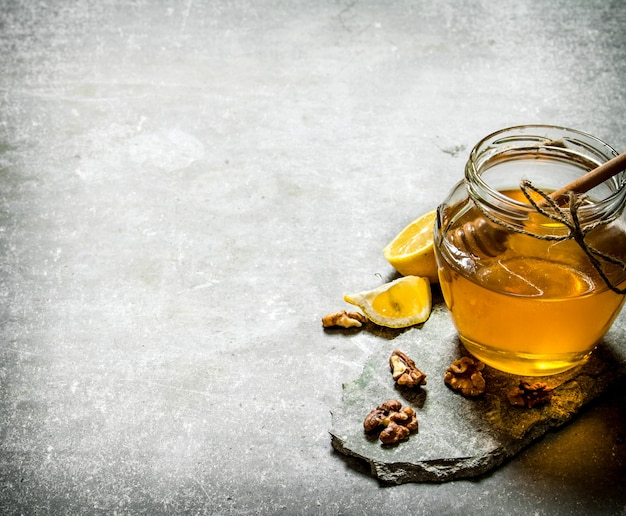 Natural honey in a jar , lemon and walnuts on a stone background