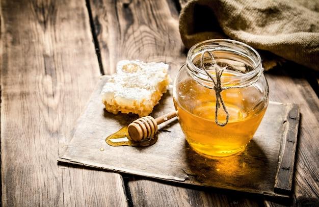 木の板に天然蜂蜜。木製の背景に。