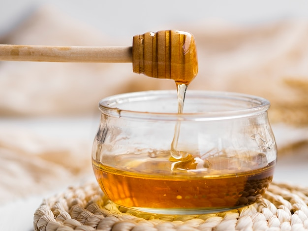 Natural honey pouring in bowl