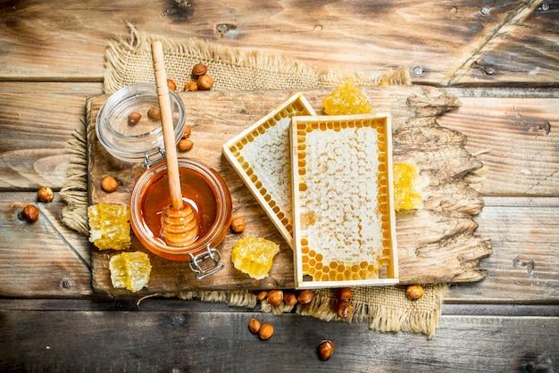 견과류와 천연 꿀. 나무 배경.