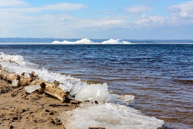 봄 날씨 동안 해안에 부서지는 자연 얼음 블록. 북극, 겨울, 봄 풍경입니다. 얼음 드리프트.