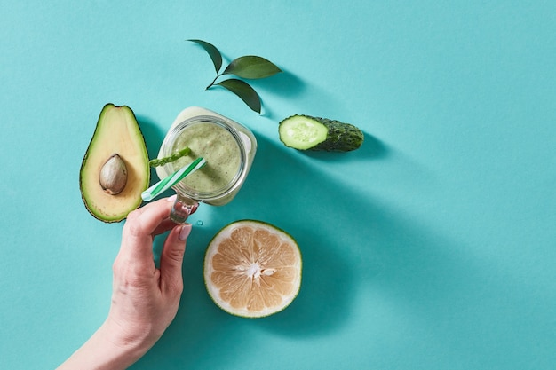 Натуральные ингредиенты для полезного смузи из авокадо с огурцом, сельдереем, шпинатом, лимоном в банке на зелени. концепция веганского и здорового питания.