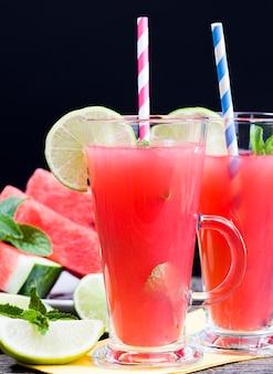 赤いスイカの果肉からの天然ジューステーブルの上のおいしくて甘いさわやかなスイカジュース自然農法からのスイカ