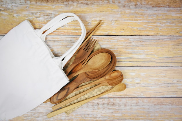 Natural kitchen tools wood products  kitchen utensils  with spoon fork chopsticks plate cutting board object and cloth bag