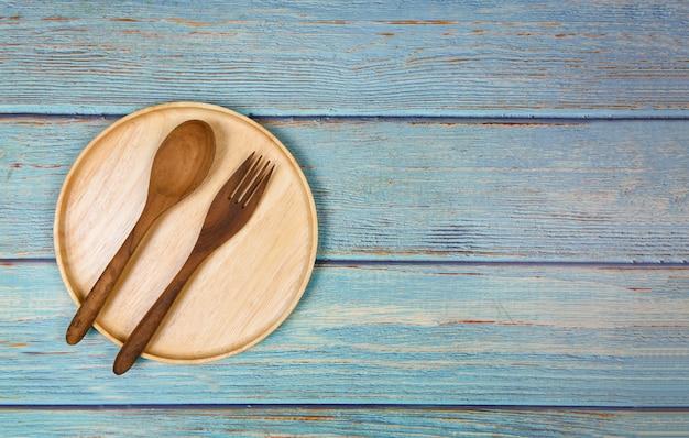 저녁 식사 테이블에있는 나무로되는 접시 숟가락 그리고 포크를 가진 자연적인 부엌 공구 목제 제품 / 주방기구