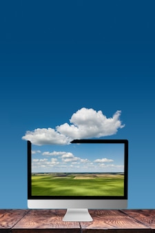 Natural landscape on a computer monitor on a wooden table against blue sky background with white cloud, copy space. working on nature, outside office work concept.