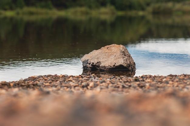 Природный ландшафт озера, высокое разрешение, движение волн на фоне леса. отражение облаков на водной ряби. на переднем плане большой камень