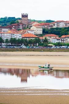ボートと村のある自然景観の海辺のシーン