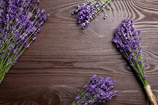 Букеты из натуральных цветов лаванды на темном деревянном фоне