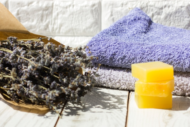 Natural lavender soap and bath salt, french oil and towels on a white wooden background