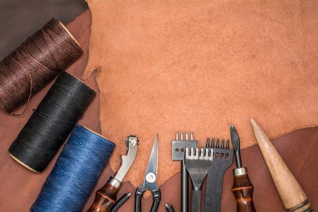 Натуральная кожа, инструменты для создания изделий и коклюшки из восковой пряжи.