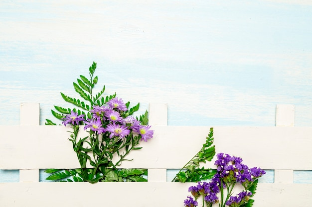 Natural leaves and flowers along white fence
