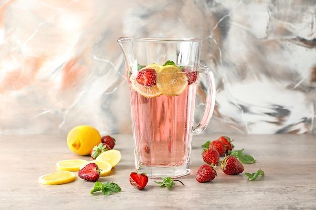 Натуральный лимонад с клубникой в стеклянном кувшине на столе