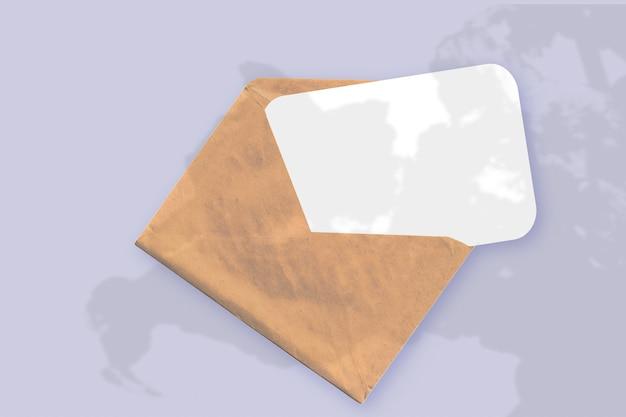 Естественный свет отбрасывает тени от растения на конверт с листом белой бумаги, лежащим на фиолетовом текстурированном фоне. макет.