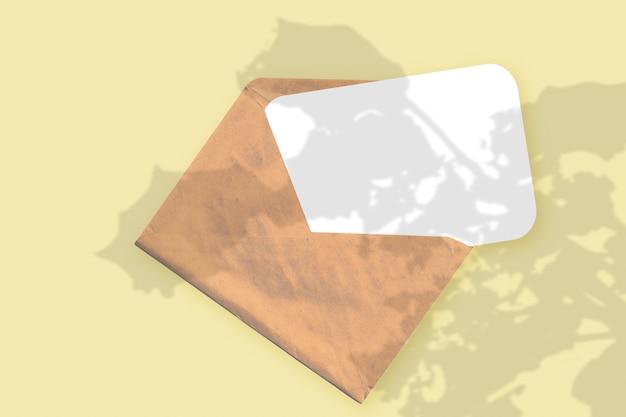 자연광은 노란색 질감의 배경에 흰 종이 한 장이 놓여 있는 봉투에 식물의 그림자를 드리웁니다. 모형.