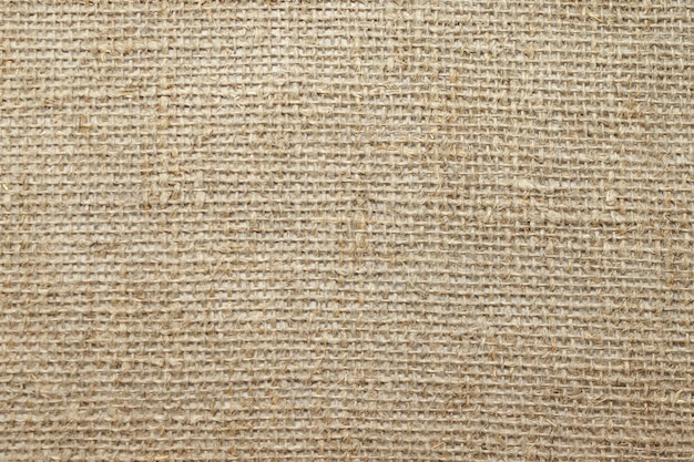 Natural linen raw uncolored textured sacking burlap . hessian sackcloth canvas woven texture. close up. selective soft focus. . text copy space.