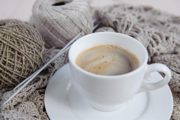 手編み用の天然リネン糸、ニット生地、一杯のコーヒー