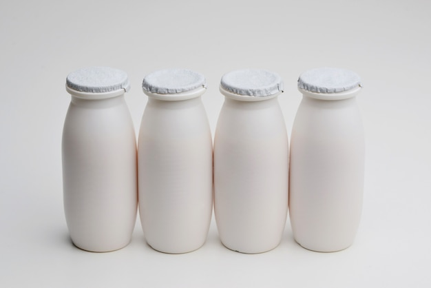 Natural liquid yogurt with probiotics in small plastic bottles on white background