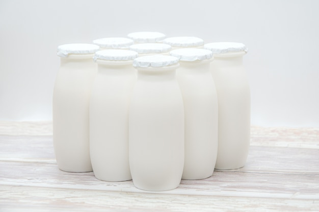 Natural liquid yogurt with probiotics in small plastic bottles on wooden table