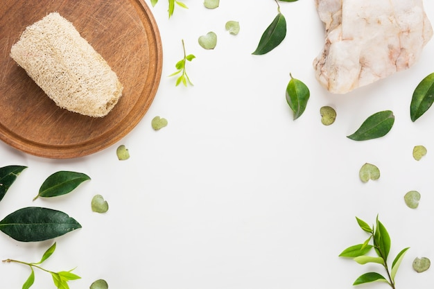 Natural loofah on wooden board with spa stone and spread leaves on white background