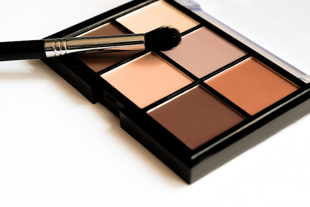 Natural look, brown tone eye shadows make up palette in black case.
