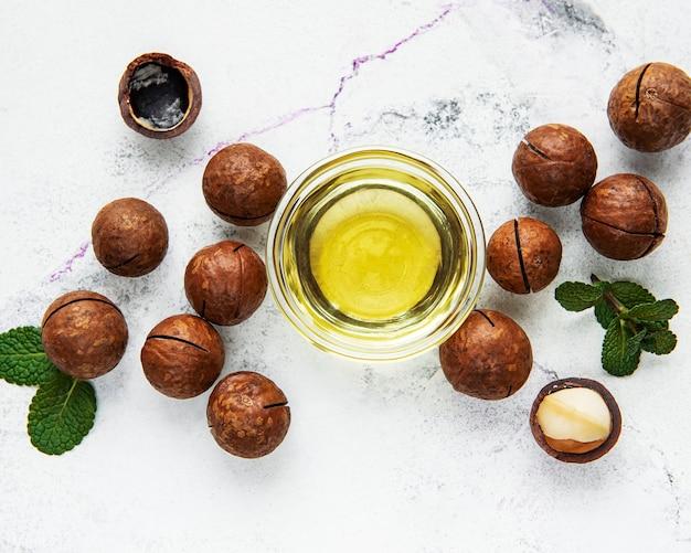 大理石のテーブルに天然マカダミアオイルとマカダミアナッツ