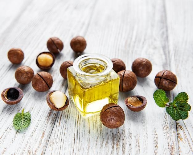 Натуральное масло макадамии и орехи макадамии на деревянной доске