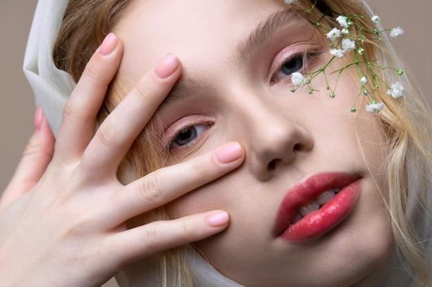 ナチュラルメイク。顔の近くの植物でポーズをとるナチュラルメイクで魅力的なモデルのクローズアップ