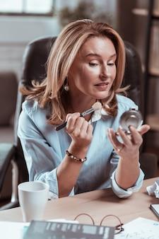 ナチュラルメイク。小さな鏡をのぞき込むナチュラルメイクのスタイリッシュで魅力的な金髪の女性