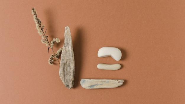 돌, 나무 및 어두운 오렌지 배경에 고립 된 마른 잔디로 천연 재료.
