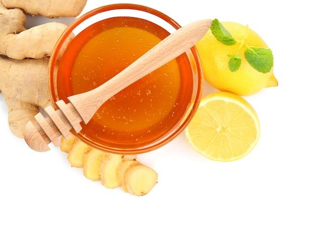 Natural medicine concept. honey, lemon and ginger on white