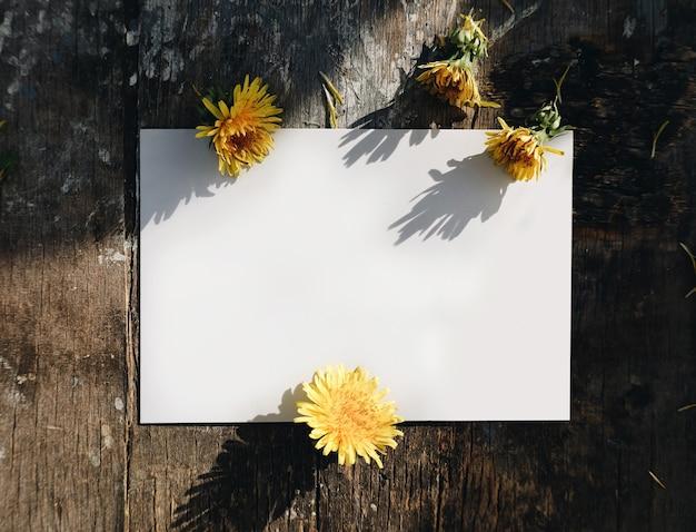 あいさつ紙カードの自然なモックアップ、木製のテーブルでタンポポと空白のはがき