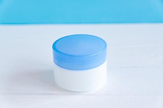 Натуральный увлажняющий или коллагеновый гель в белой пластиковой банке на белом деревянном фоне. спа-косметика и концепция ухода за кожей крупным планом.