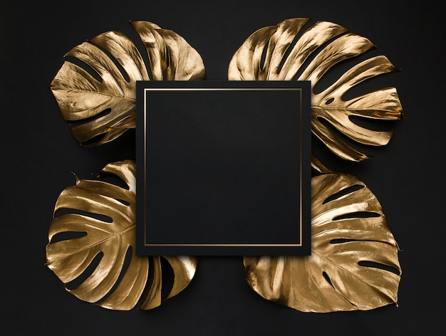 Natural monstera leaves spray painted with gold metallic paint and a black empty note