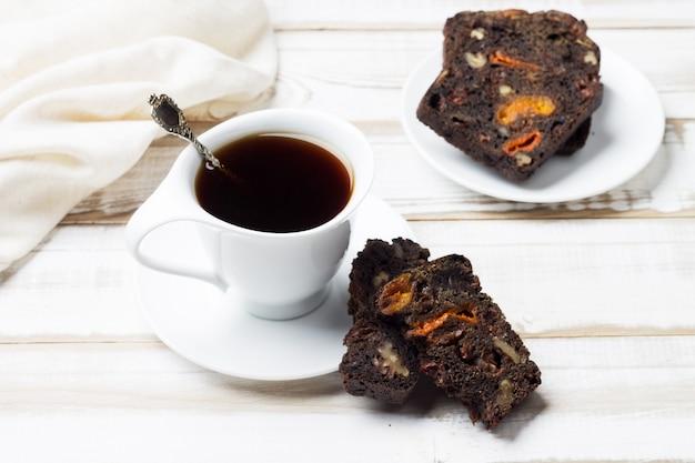 Натуральный утренний напиток из цикория в белой чашке и блюдце с кусочками фруктово-орехового хлеба.
