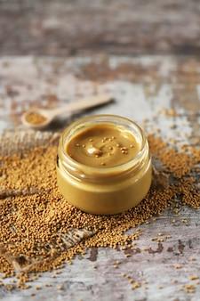 Natural mustard in a jar. grains of mustard. homemade mustard. organic mustard. selective focus.