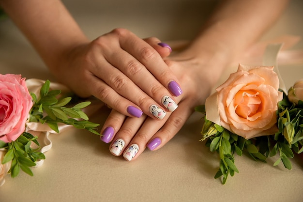 Natural nails with beautiful manicure with blossom flowers