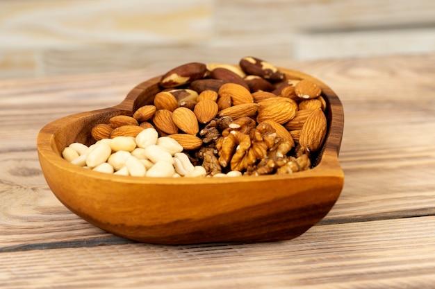 茶色の木製テーブルにハートのシンボルの形をした木のプレートにさまざまなナッツの自然な栄養ブレンド