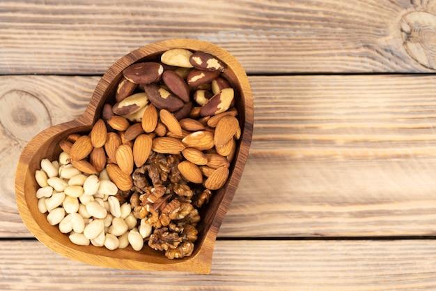 갈색 나무 테이블에 심장 기호 모양의 나무 접시에 다양한 견과류의 자연 영양 조화