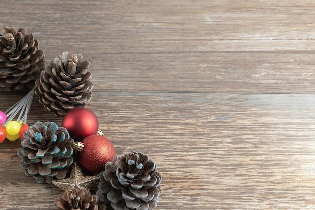 Coni di quercia naturale su un ponte di legno con ornamenti scintillanti intorno