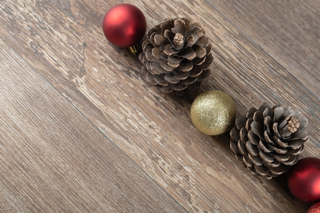 Natural oak tree cones on a wooden deck with glittering ornaments around