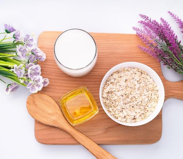 Натуральные овсяные хлопья, цветы, стакан молока и меда