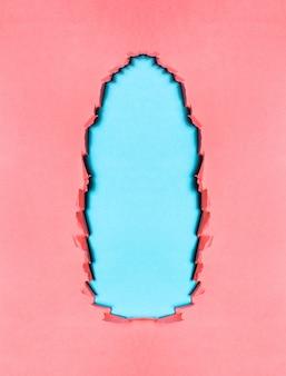 青い色の背景に破れたピンクの織り目加工の紙の自然。